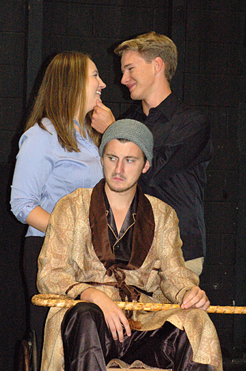 """Angélique (Tessa Lee, who is majoring in theatre and nursing) and her love interest, Cléante (Michael Miller, who is majoring in bioengineering), share a stolen moment under the disapproving watch of her father, Argan (Carter Makiewicz, a theatre major) in this scene from the UT production of Molière's """"The Imaginary Invalid."""""""