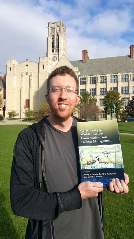 """Dr. Henry Streby posed with his book, """"Golden-Winged Warbler Ecology, Conservation and Habitat Management,"""" on Main Campus."""