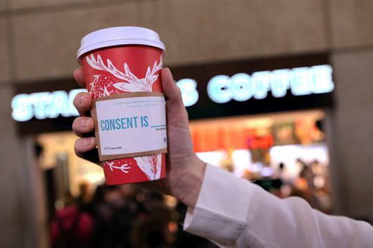"Lindsay Tuttle, head of Sexual Assault Early Prevention Program (SAEPP), holds a Starbucks Coffee cup with a Coffee Sleeve that says ""Consent is ..."""
