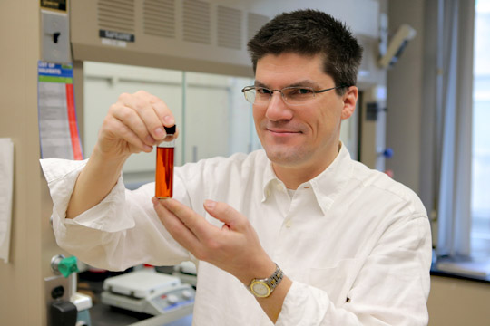 Dr. Terry Bigioni, professor in the Department of Chemistry and Biochemistry, held a vial of silver nanoparticles in liquid form.