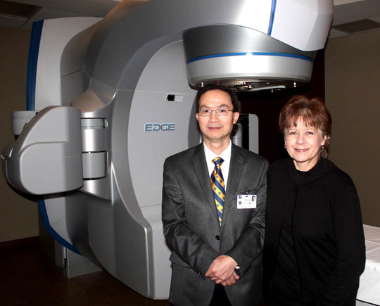 Dr. Changhu Chen and Gerri Musser posed for a photo in the Edge Radiosurgery Suite in UT Medical Center's Eleanor N. Dana Cancer Center. Under Chen's care, Musser received a 10-day, high-dose, targeted radiation treatment for a tumor in her pancreas, liver, stomach and bile duct.