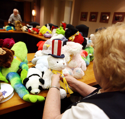 A member of the Satellites Auxiliary tied UT ribbons on stuffed animals  that will be given to children in the UT Medical Center Emergency  Department. ce89bfd25d6c