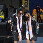 Graduates Megan Stevenson and Adrienne Heckman walk with arms around each other in commencement regalia