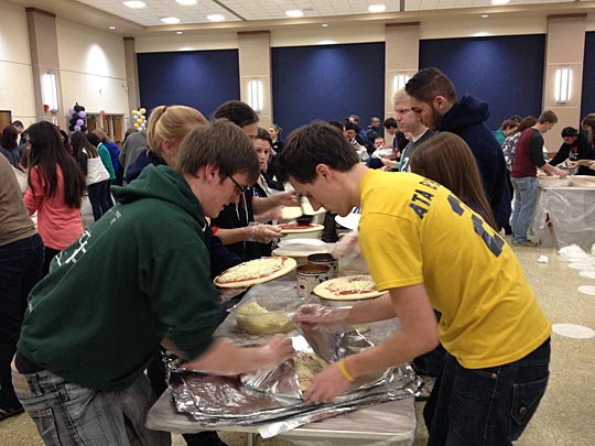 Students assembled pizzas last year to help feed the homeless.