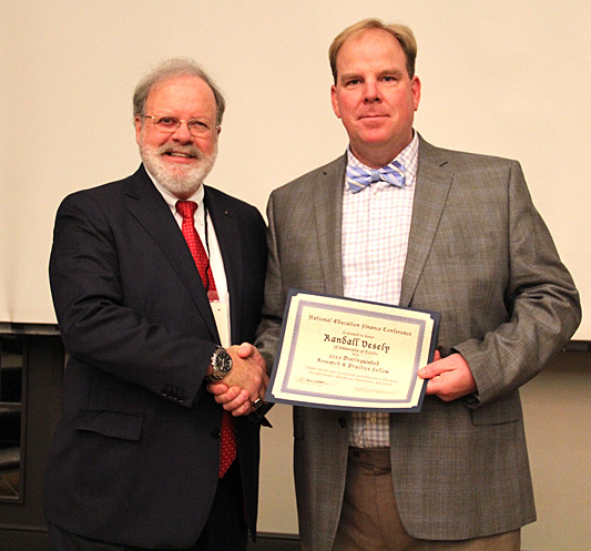 Dr. Randall Vesely, UT assistant professor of educational administration and supervision, right, received the Distinguished Fellow of Research and Practice Award last month from Dr. Craig Wood, University of Florida professor and president of the National Education Finance Association.