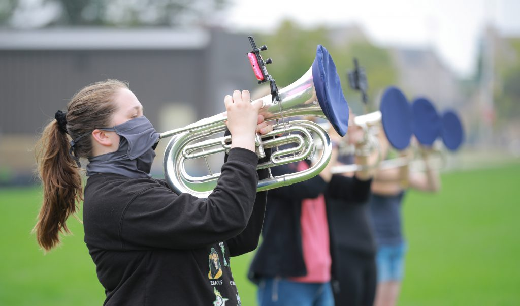 Lauren Weinberg plays the mellophone during marching band rehearsal