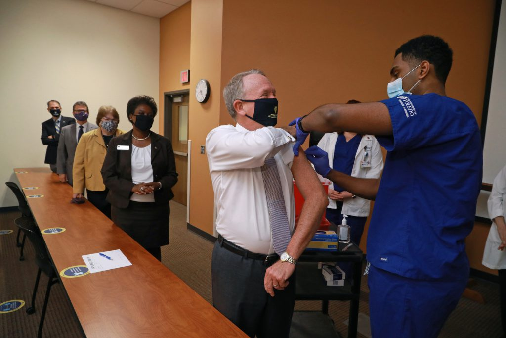 Interim President Gregory Postel receives his flu shot from nursing student