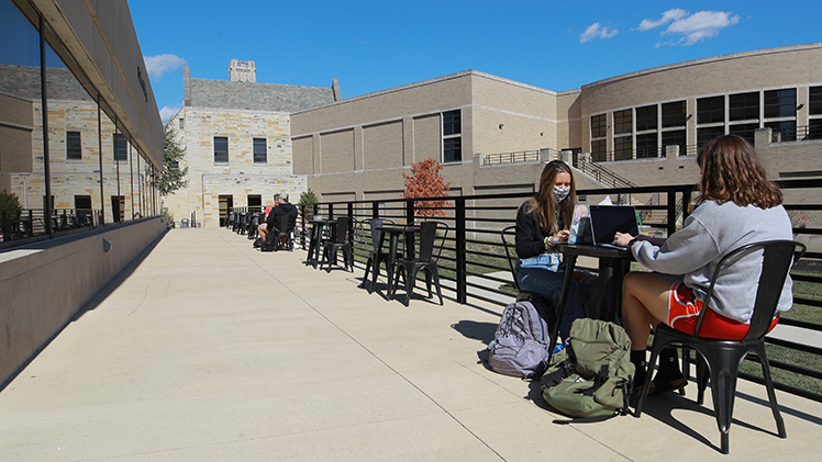 Students sit at small tables in new outdoor seating area outside Carlson Library
