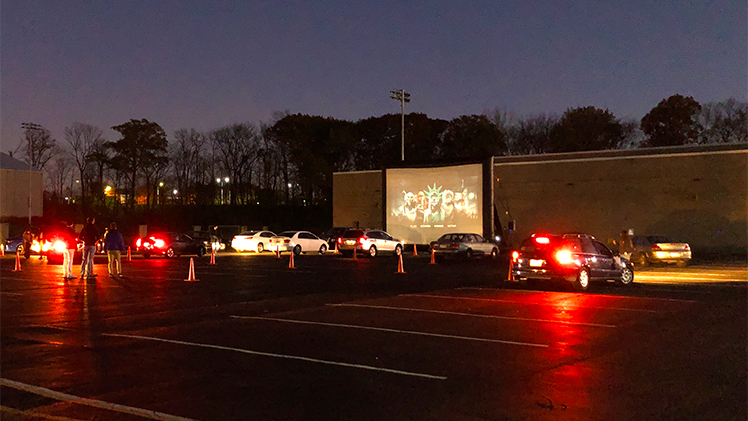 Cars line up outside Health Education Building for Drive-In Movie on Halloween