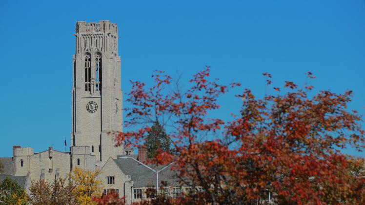 University Hall tower with red fall leaves in foreground