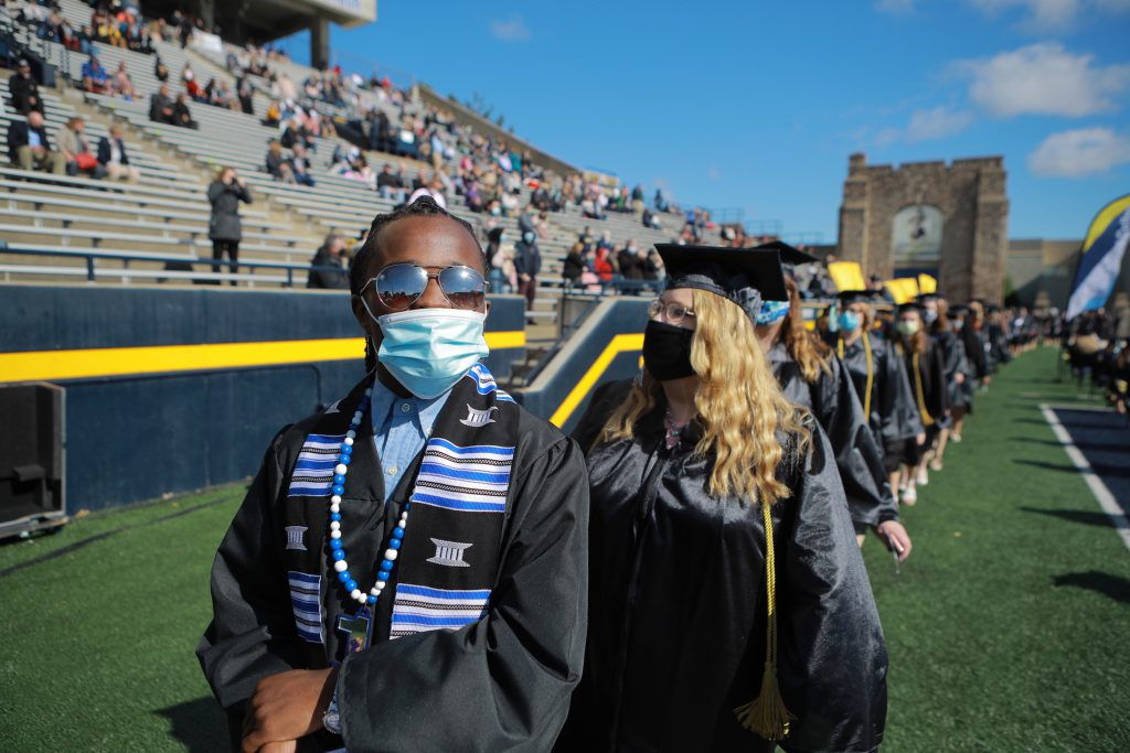 Daire'yon Watson wearing sunglasses leads a line of graduates in the Glass Bowl
