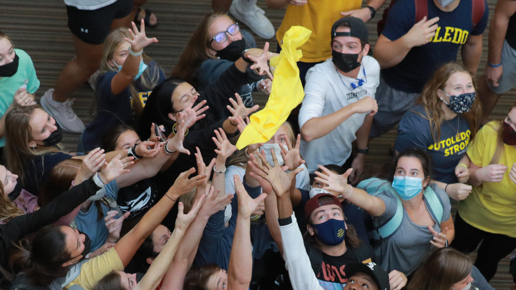 Students catch UToledo gear dropped from the third floor of Memorial Field House